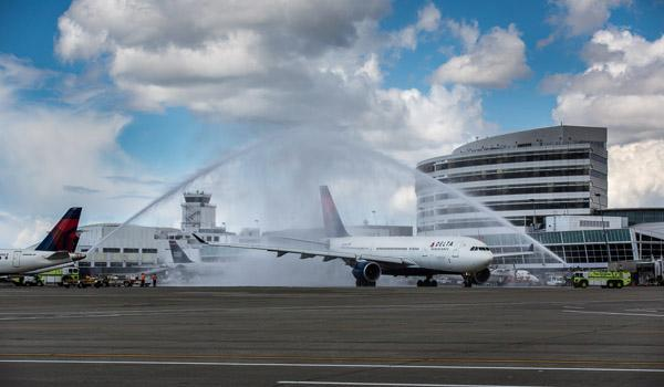 Port of Seattle fire trucks salute a Delta Airbus A330 as it departs for Hong Kong on Monday.