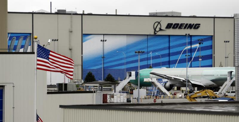 In this photo taken Wednesday, May 29, 2013, a jet is parked in view of a giant bay door of the Boeing production facility in Everett, Washington.