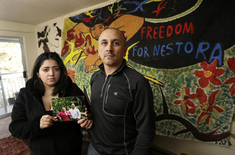 Grisel Rodriguez, left, and Jose Avila, right, pose for a photo, Tuesday, Nov. 26, 2013, in their apartment in Renton, Wash. They are holding a photo of Avila with his wife, Nestora Salgado, who has been detained since she was arrested Aug. 21, 2013.