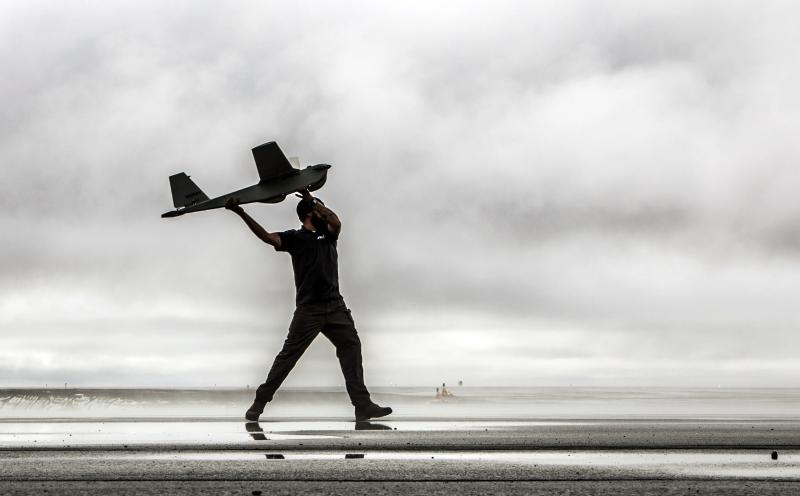 In this undated photo provided by AeroVironment, a man hand-launches a Puma drone aricraft.