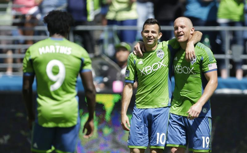 The Sounders' Chad Barrett, right, celebrates with teammates Marco Pappa and Obafemi Martins, (9) after Barrett scored a goal against Real Salt Lake Saturday, May 31, 2014, in Seattle. Pappa and Martins also had goals as the Sounders beat RSL 4-0.
