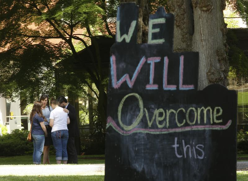 "A group of people pray together near a sign on the Seattle Pacific University campus that reads ""We Will Overcome This,"" Friday, June 6, 2014 in Seattle, the day after a shooting took place at Otto Miller Hall at the school."