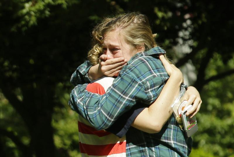 Two women embrace near a prayer circle on the campus of Seattle Pacific University, Friday, June 6, 2014 in Seattle