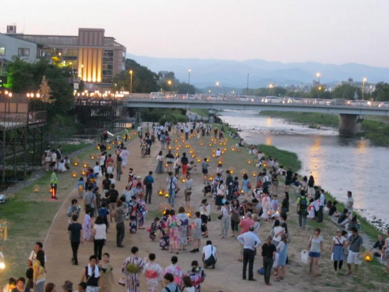 Yes, you should see the big sights. But pausing just to look at the everyday things nearby — like this evening gathering near a river in Kyoto, Japan — can add a lot to your sense of a new place.