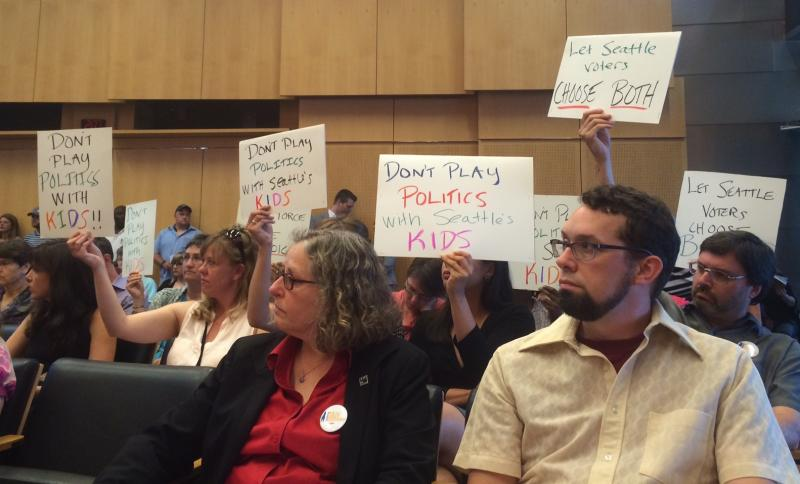 Supporters of I-107 silently protest a Seattle City Council vote to pit the initiative they favor against a city-endorsed preschool pilot proposal at a meeting in June 2014.