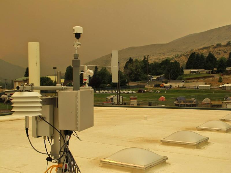 A portable, temporary air monitor was placed on the roof of the high school in Entiat, Washington and has been collecting samples since Thursday. Note the ground-hugging wildfire smoke in background.