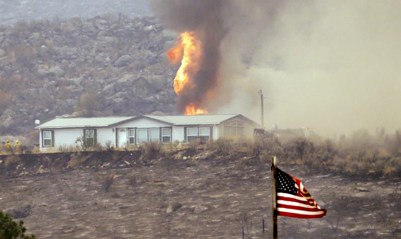 Flames shoot from behind a house during a wildfire Friday, July 18, 2014, near Pateros, Wash.