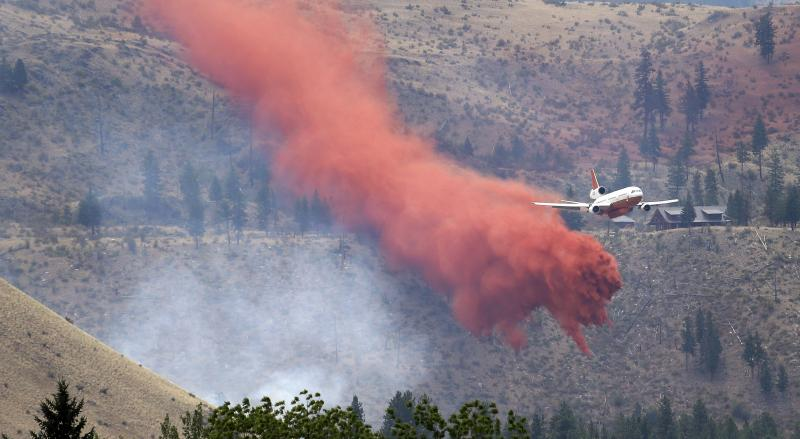 A DC-10 air tanker pulls up after dropping fire retardant over a wildfire Saturday, July 19, 2014, near Carlton, Washington.