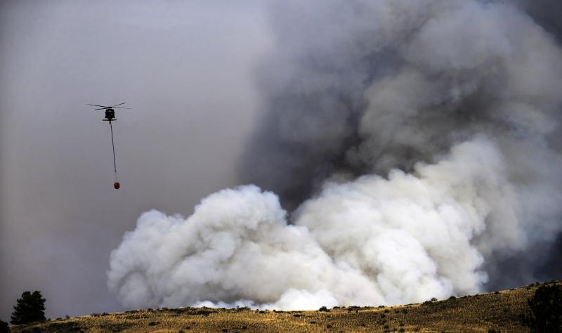A helicopter preparing to drop water is dwarfed by a billowing cloud of smoke from a wildfire Friday, July 18, 2014, in Twisp, Wash. A fire racing through rural north-central Washington destroyed about 100 homes.