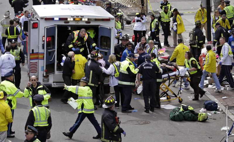 Medical workers aid injured people after two bombs exploded near the finish line of the Boston Marathon in Boston, April 15, 2013.
