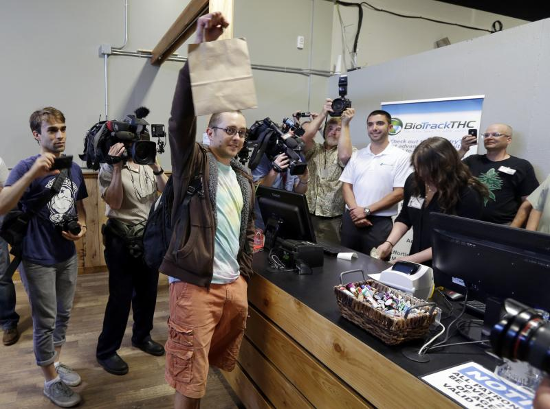 Cale Holdsworth, of Abeline, Kan., holds up his purchase after being the first in line to buy legal recreational marijuana at Top Shelf Cannabis, Tuesday, July 8, 2014, in Bellingham, Wash. Holdsworth had been in line since 4:00 a.m.