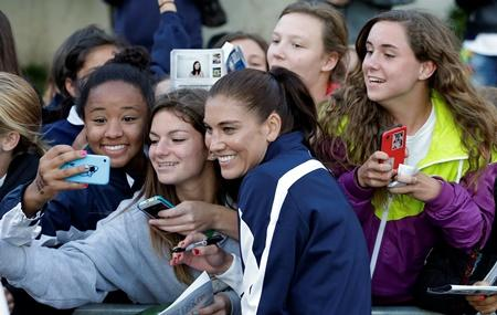 Seattle Reign FC goalie Hope Solo, center, poses for photos with fans after an NWSL soccer game against Sky Blue FC on Saturday, June 28, 2014, in Seattle.