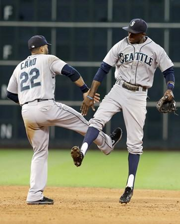 The Mariners' Robinson Cano (22) and James Jones celebrate their 5-2 win over the Houston Astros to sweep the three-game series on Wednesday, July 2, 2014, in Houston.
