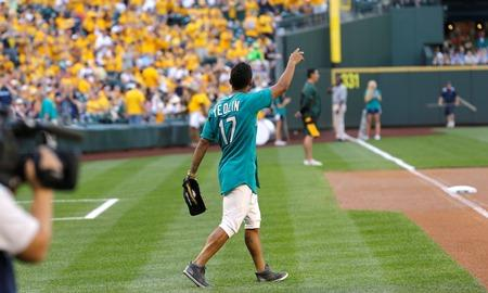 Seattle Sounders' DeAndre Yedlin waves to fans before throwing out the first pitch of a baseball game between the Seattle Mariners and the Oakland Athletics, Friday, July 11, 2014, in Seattle.