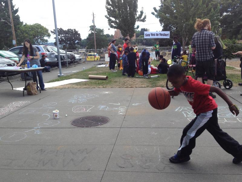 "Yesler Terrace resident plays basketball at ""Say Yes To Yesler"" party on Saturday, July 19, 2014."