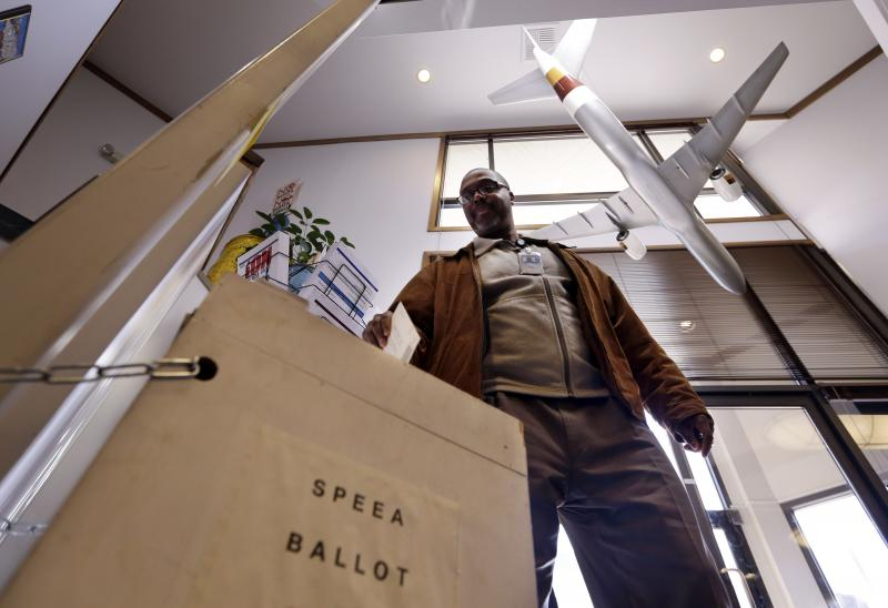 FILE - With a model 757 over his shoulder, Ernest Griffin drops his ballot at the headquarters of the union for Boeing Co.'s engineers and technical workers, Tuesday, Feb. 19, 2013, in Tukwila, Washington.