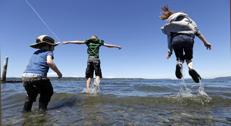 Ainsley MacDonald, right, and Will Walker, 10, try to leap above incoming waves as Calister MacDonald, left, 3, looks on Tuesday, July 1, 2014, at a beach on the Puget Sound in Mukilteo, Washington.