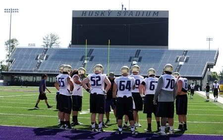 UW's offensive linemen huddle near the end zone of Husky Stadium during the first session of NCAA college football practice before the upcoming fall season, Aug. 4, 2014, in Seattle.