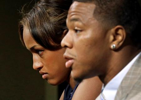 Janay Rice, back left, looks on as her husband, Baltimore Ravens running back Ray Rice, speaks during a news conference May 23, 2014. Ray Rice spoke to the media for the first time since his arrest for assaulting his then-fiance at a casino.
