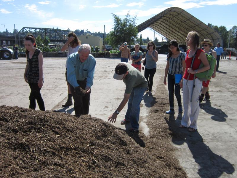 Dan Thompson, manager of wastewater operations for the City of Tacoma, shows students a pile of freshly-cut mulch the city's TAGRO plant produced out of yard waste. The plant also uses pasteurized wastewater byproducts to create lawn and garden soils.