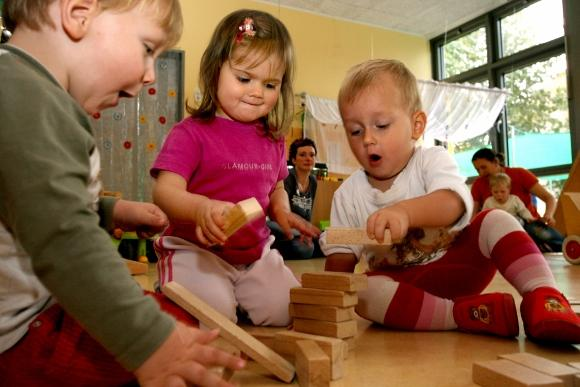 Toddlers play in a kindergarten classroom.
