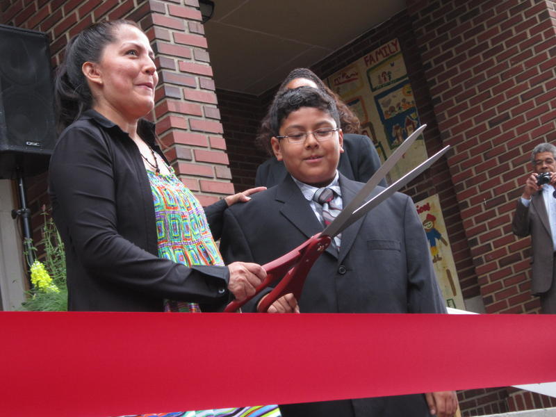 The parent of a student at Seattle's First Place Scholars Charter School prepares to cut a ribbon at a ceremony marking the school's opening in 2014.