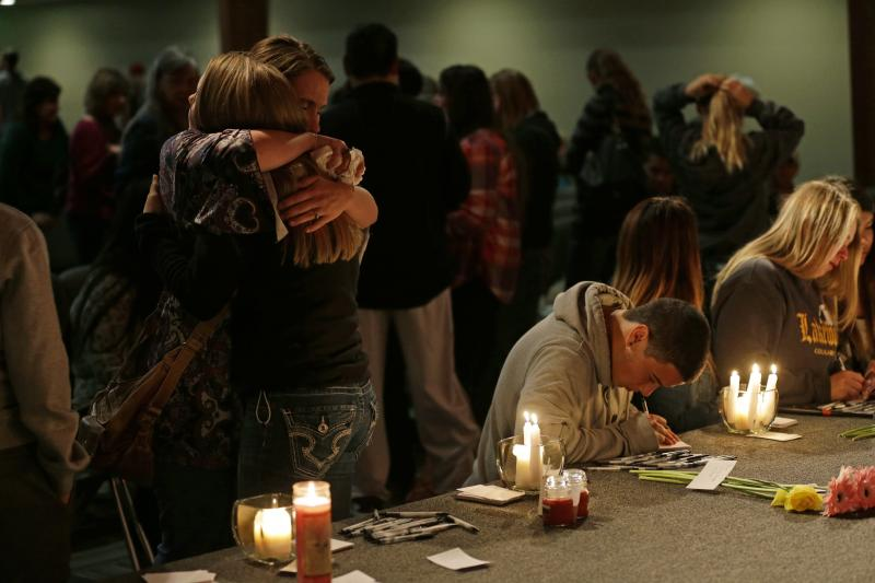 Two people hug as others write messages on paper following a memorial vigil at the Grove Church in Marysville, Wash., Friday, Oct. 24, 2014, for people affected by a shooting at Marysville Pilchuck High School earlier in the day.