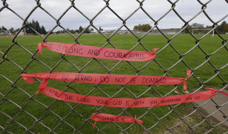 Ribbons with a Bible verse written on them are tied to a fence Monday, Oct. 27, 2014 at a growing memorial at Marysville Pilchuck High School in Marysville, Washington.