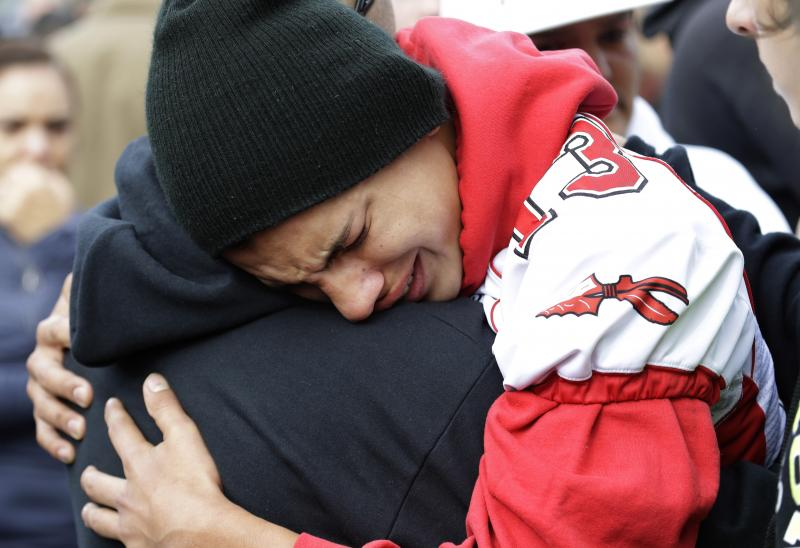 A student wearing a Marysville Pilchuck football jersey is comforted at a church Friday, Oct. 24, 2014, where students were taken to reunite with parents following a shooting at Marysville Pilchuck High School in Marysville, Washington.