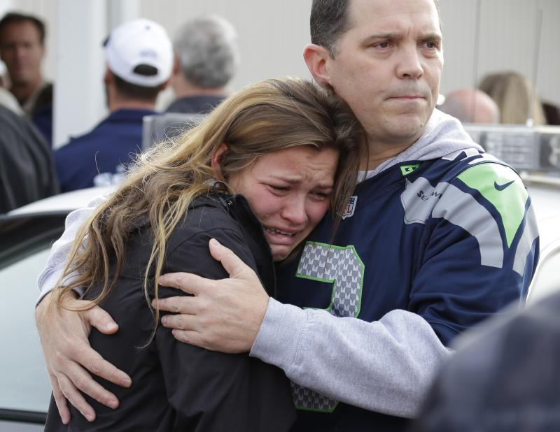 People react as they wait at a church, Friday, Oct. 24, 2014, where students were taken to be reunited with parents following a shooting at Marysville Pilchuck High School in Marysville, Washington.
