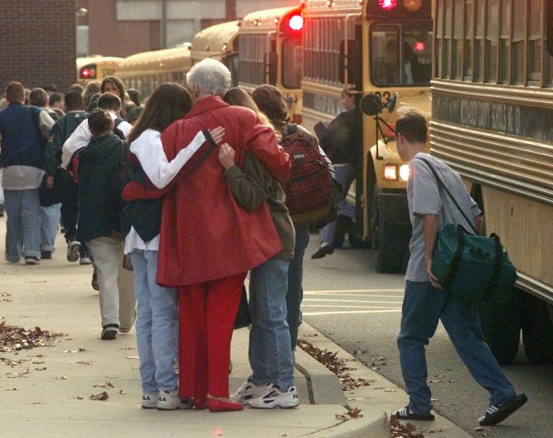 Students arriving at Heath High School in West Paducah, Kentucky embrace an unidentified adult on Tuesday, Dec. 2, 1997.