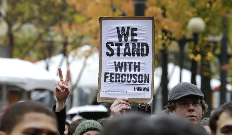 "A protester holds a sign that reads ""We Stand With Ferguson,"" during a march in downtown Seattle, Tuesday, Nov. 25, 2014, to demonstrate against a grand jury's decision not to indict police officer Darren Wilson in the killing of Michael Brown."