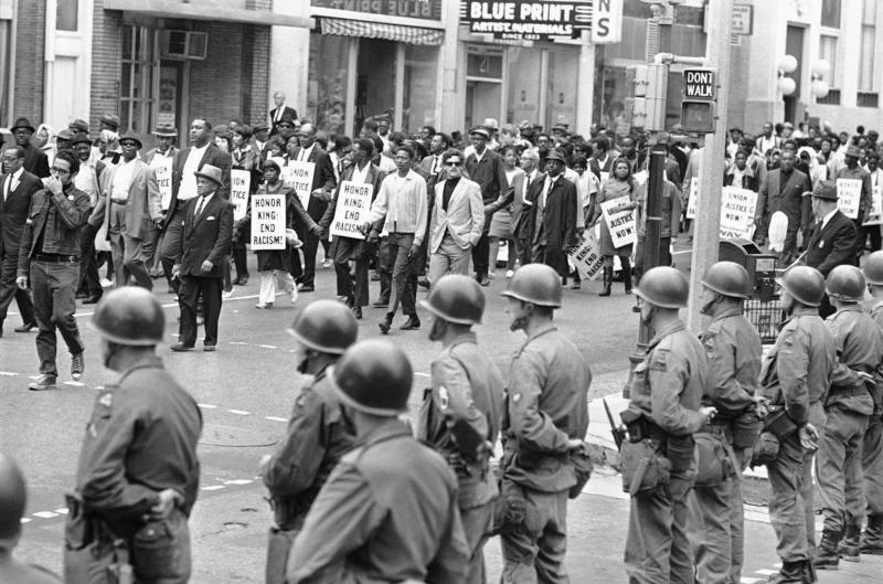With members of the Tennessee National Guard standing ready, thousands of people march in honor of Dr. Martin Luther King, in Memphis, Tennessee on April 9, 1968.