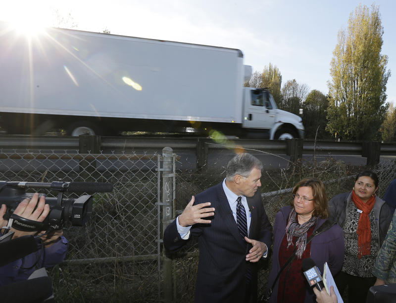 """Washington Gov. Jay Inslee, center, stands on a bike and pedestrian path in Seattle's South Park neighborhood, Monday, Nov. 17, 2014. The stop was part of a """"climate tour"""" to raise awaremess for health impacts of greenhouse gas emissions."""