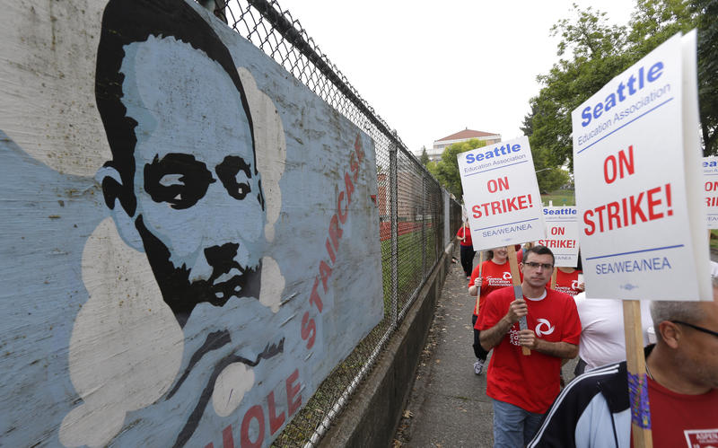 Striking Seattle School District teachers and other educators walk a picket line past an image of Martin Luther King Jr., at Franklin High School in Seattle on September 10, 2015.