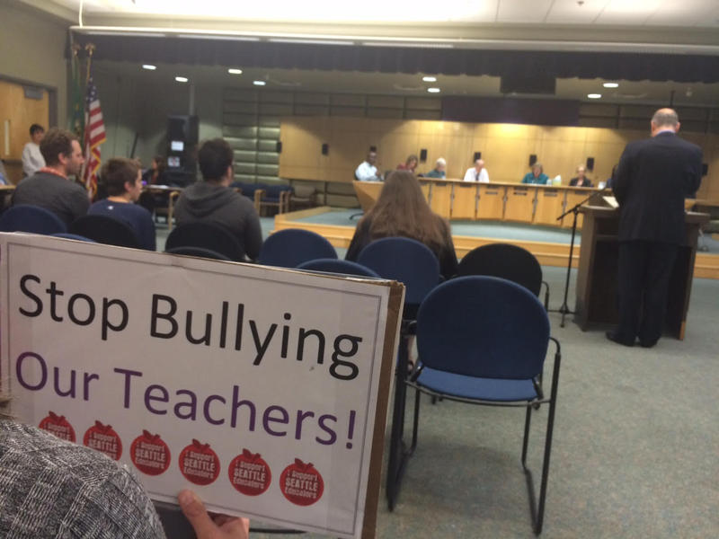 Parents supporting members of the teachers union, the Seattle Education Association, hold signs during a special meeting of the Seattle school board Tuesday night.
