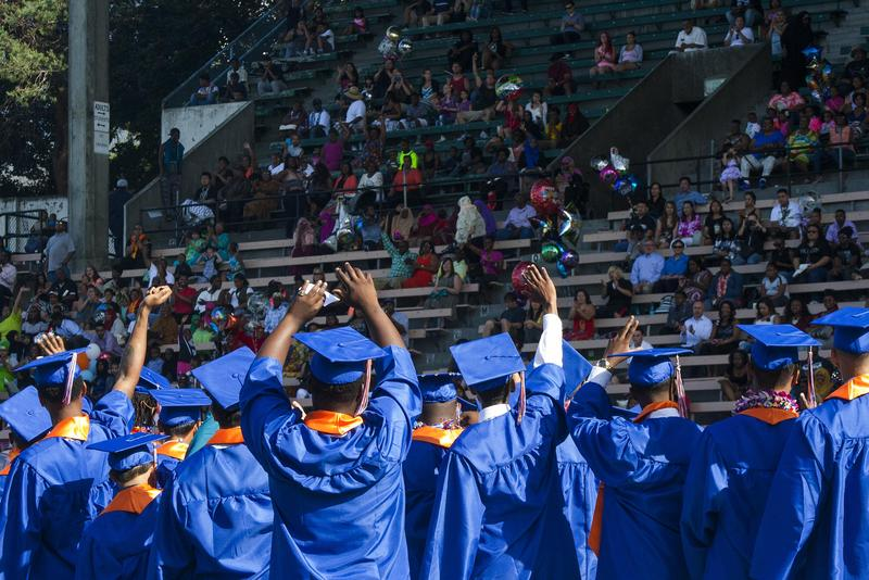 Rainier Beach High School seniors wave to the crowd watching their graduation ceremony in the stands of Memorial Stadium at Seattle Center in June 10, 2015. The district reports more than 84 percent of the Class of 2015 graduated on time.