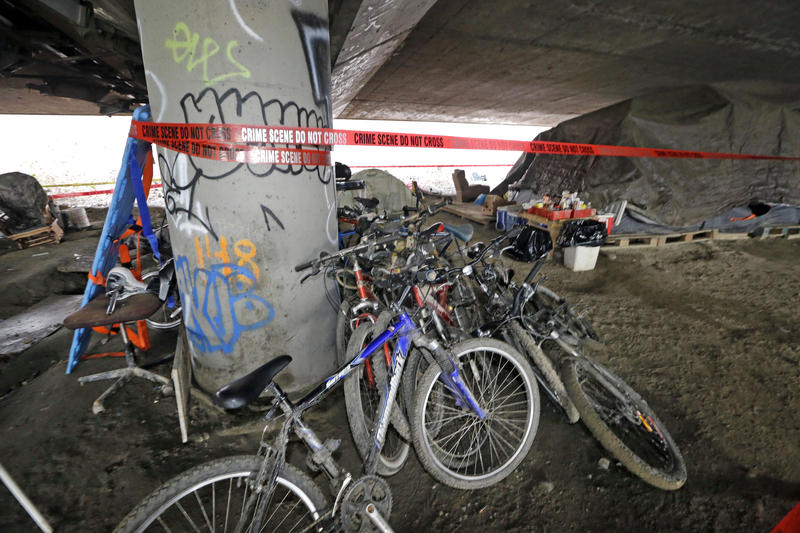 Bicycles remain stacked against a support post for Interstate 5 above as crime scene tape surrounds the site of a shooting the night before at a homeless encampment, Wednesday, Jan. 27, 2016, in Seattle.