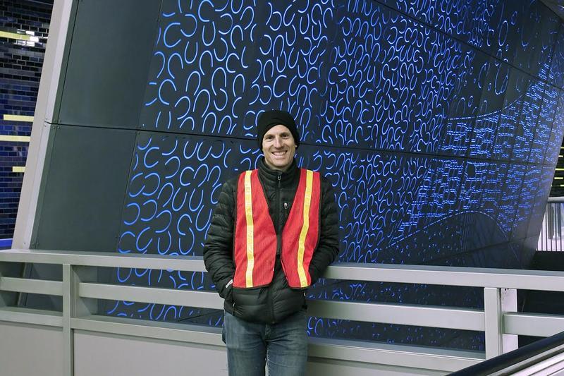 "Artist Leo Berk stands in the University of Washington Link Light Rail Station. Berk's ""Subterranium"" is in the background."