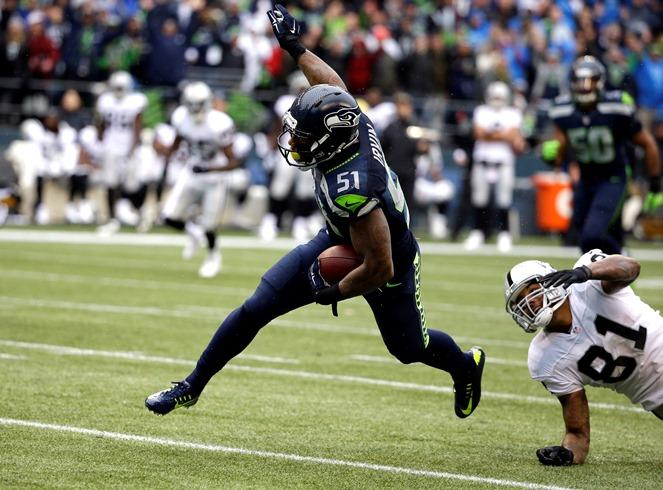 You can see why they need him. Now-former Seahawks outside linebacker Bruce Irvin (51) runs the ball as Oakland Raiders' Mychal Rivera (81) looks on after Irvin intercepted and ran for a touchdown on Nov. 2, 2014. Irvin signed with the Raiders this week.