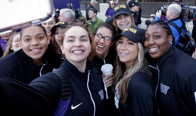 Washington players huddle together for a selfie during a sendoff rally for the UW women's basketball team Thursday in Seattle. Washington plays Syracuse in a national semifinal at the Final Four of the NCAA Tournament Sunday in Indianapolis.