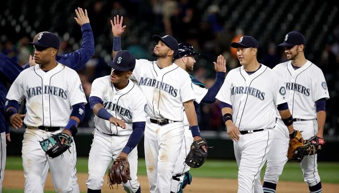 Mariners players share congratulations after the team beat the Tampa Bay Tuesday, May 10, 2016, in Seattle. The Mariners won 6-4.