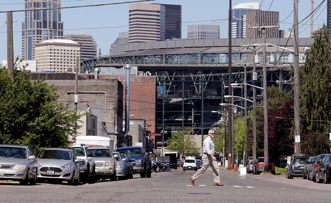 A pedestrian walks across Occidental Ave. South and in view of Safeco Field behind, Monday, May 2, 2016, in Seattle.