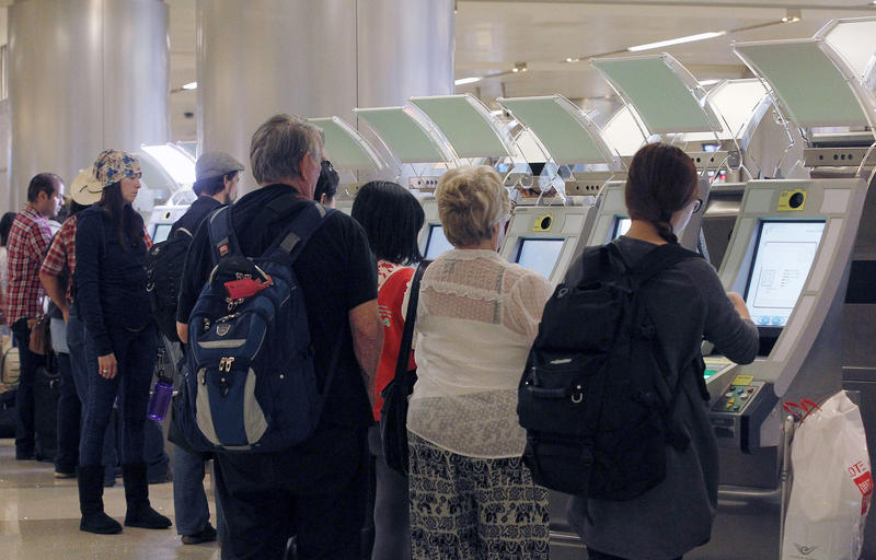 Passengers arriving from abroad at Los Angeles International Airport use automated passport kiosks in 2014.