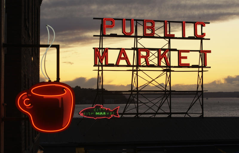 A neon coffee cup and the iconic sign for Seattle's Pike Place Market are seen at sunset, Friday, Nov. 13, 2009.