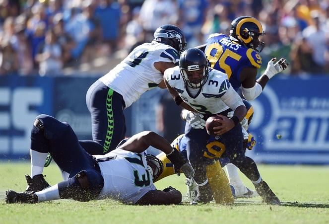 Seahawks quarterback Russell Wilson (3) scrambles while under pressure from the Rams at the Los Angeles Memorial Coliseum, Sunday, Sept. 18, 2016.