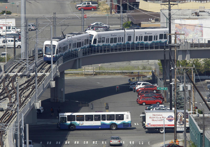 A Sound Transit train passes over a Sound Transit bus in Seattle.