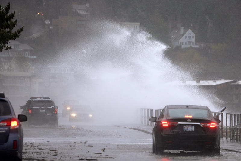 FILE: A wind-blown wave comes up and over the seawall and into traffic Tuesday, Nov. 17, 2015, in the West Seattle neighborhood of Seattle.