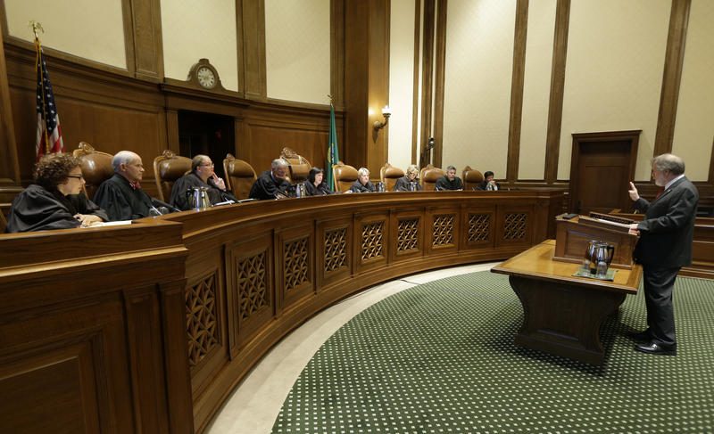 Alan Copsey, right, a deputy attorney general for the state of Washington, speaks during a hearing before the Washington State Supreme Court regarding a lawsuit against the state over education funding, Wednesday, Sept. 7, 2016, in Olympia, Wash.