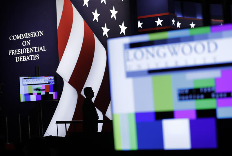 An official stands on stage during preparations for the vice-presidential debate between Republican vice-presidential nominee Gov. Mike Pence and Democratic vice-presidential nominee Sen. Tim Kaine in at Longwood University in Farmville, Va., Monday, Oct.